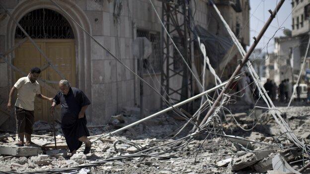 Palestinian men walk amidst debris following an Israeli military strike in Gaza city, on July 23, 2014.