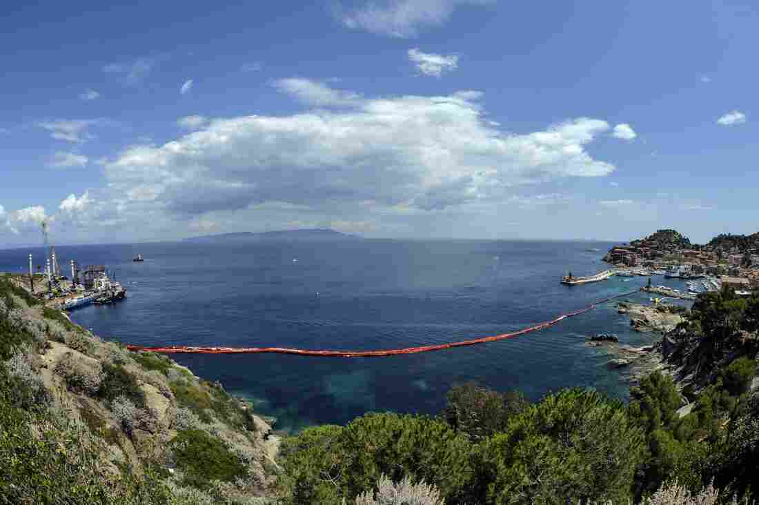 The harbor of the Italian island of Giglio, after the wreck of the Costa Concordia was towed away. Italy's once-luxurious cruise liner embarked on its last voyage on Wednesday.