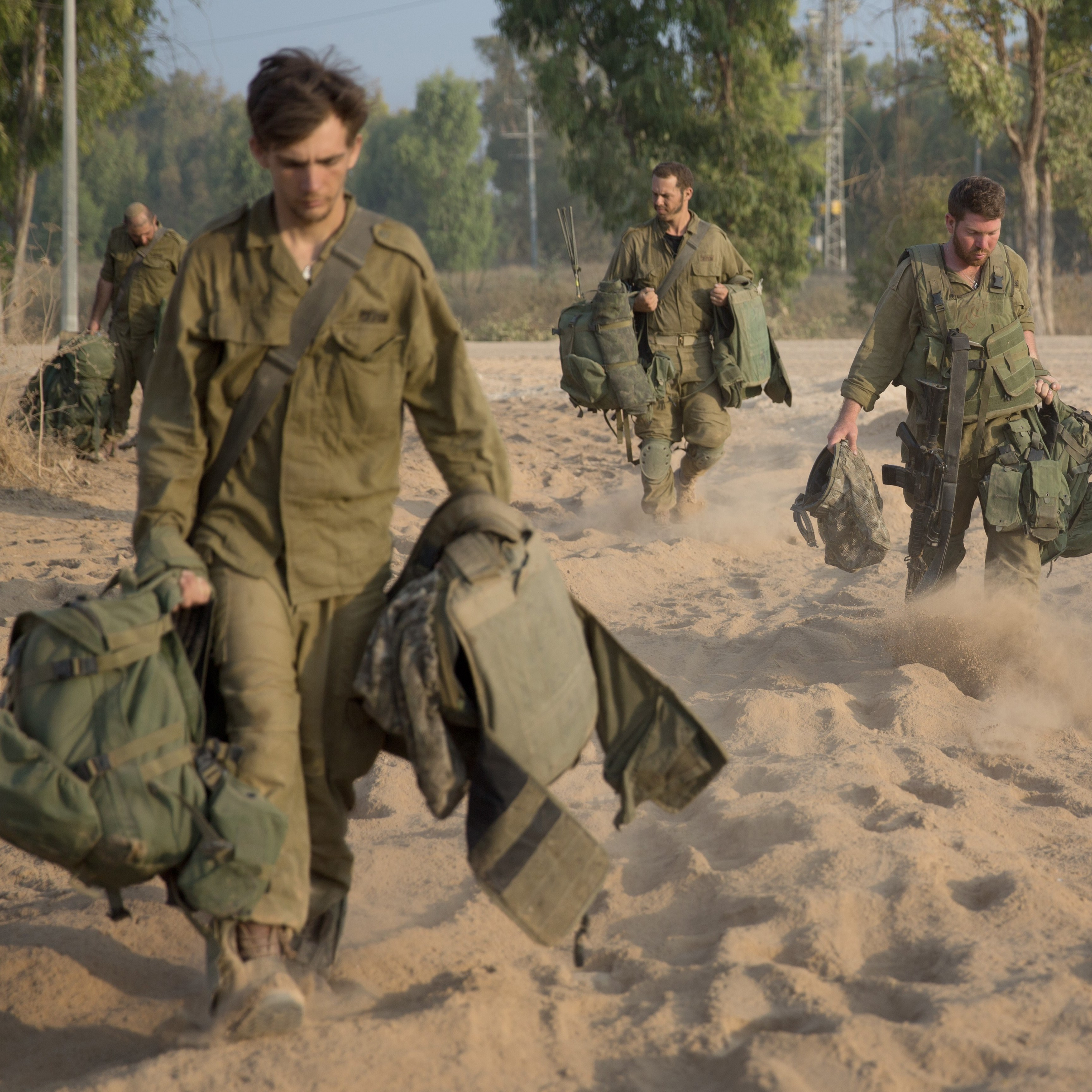 Israeli soldiers return from the Gaza Strip at an army deployment area near Israel's border with the besieged Palestinian territory on July 23, 2014, as the conflict entered its third week with neither side showing any sign of willingness to pull back.