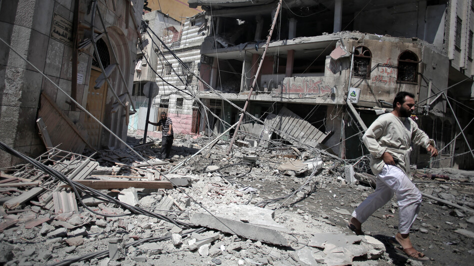 Palestinians walk through the rubble of houses in Gaza City minutes after they were hit in an Israeli strike on Wednesday. (AP)