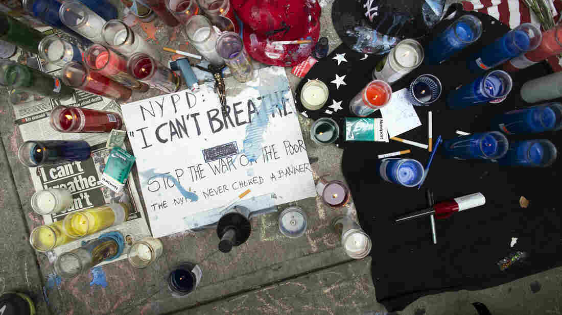 A memorial for Eric Garner rests on the pavement near the site of his death. The poster on the ground quotes Garner; video of the arrest shows him telling police officers he couldn't breathe, shortly before he lost consciousness.