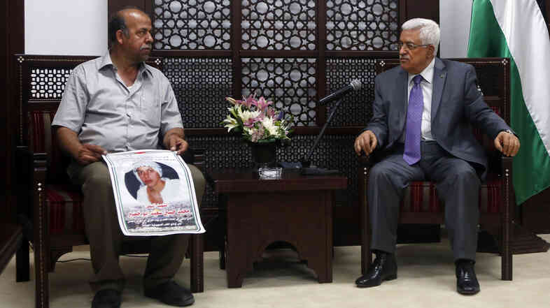 Hussein Abu Khdeir (left), father of slain Palestinian teenager Mohammed Abu Khdeir, holds a photo of his son as he meets with Palestinian Authority President Mahmoud Abbas in the West Bank earlier this month. Israel has charged three Jewish Israelis with the killing and ruled that it was a terror attack. This has drawn criticism from some in Israel.