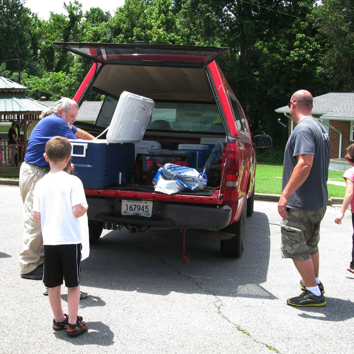 Volunteer Steve Boyd (left) distributes lunches to children from a YMCA truck with the help of YMCA employee Sean Summers (second from right) in Hopkins County, Ky.