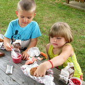 Logan Kovach, 6, Matthew Kovach, 2, and Allyson Kovach, 5, eat a lunch distributed by the YMCA in Hopkins County, Kentucky.