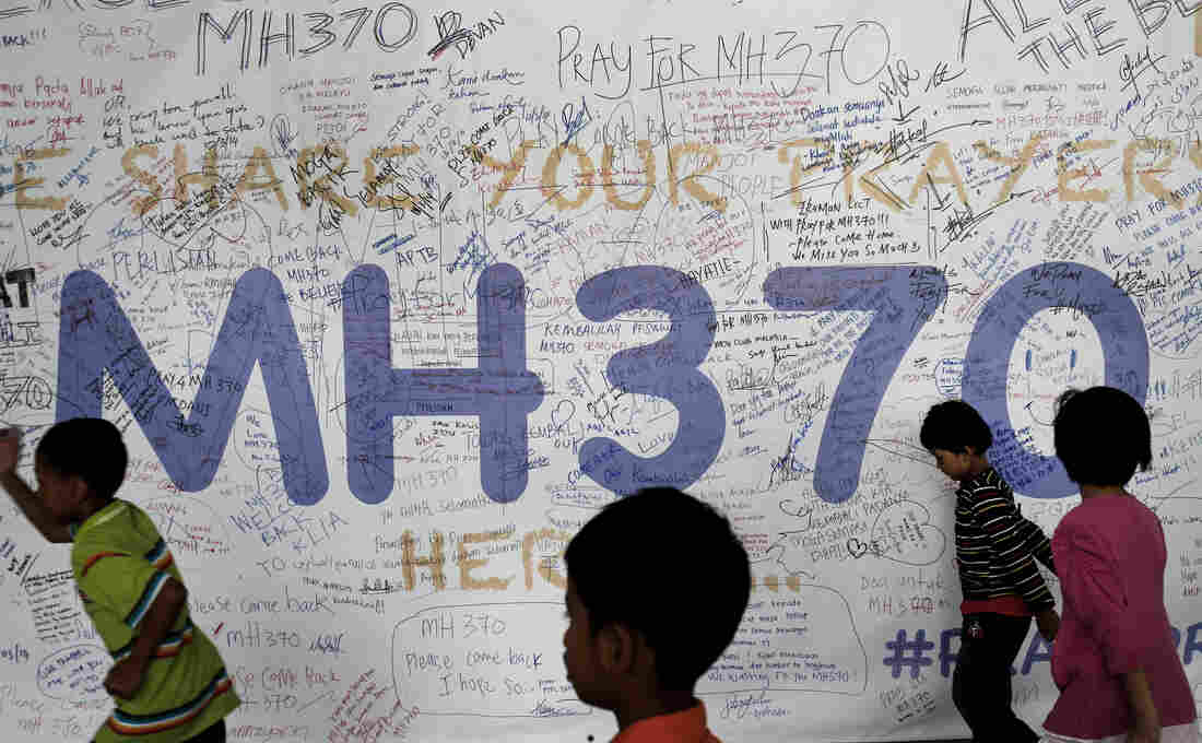 Children run past dedication messages and well wishes displayed for passengers and others involved with the missing Malaysia Airlines jetliner MH370 on the walls of the Kuala Lumpur International Airport, on March 13.