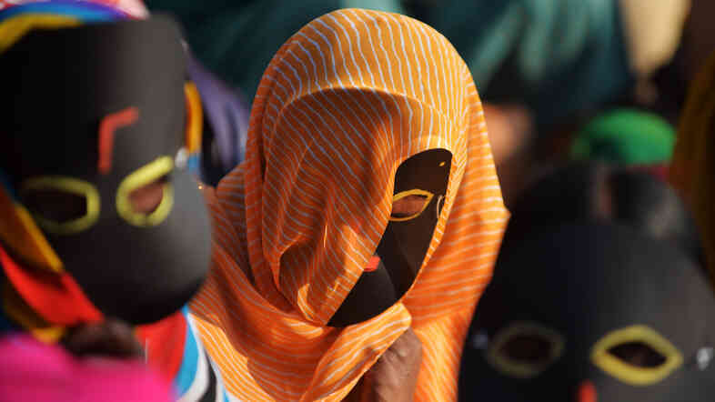 Masked Indian sex workers protest alleged police atrocities in Bangalore last year.
