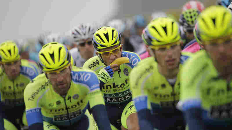Spain's Alberto Contador eats a banana in as he rides in the pack during the sixth stage of the Tour de France on July 10, 2014. The cyclists aim to eat up to 350 calories an hour as they ride, and up to 9,000 calories a day.