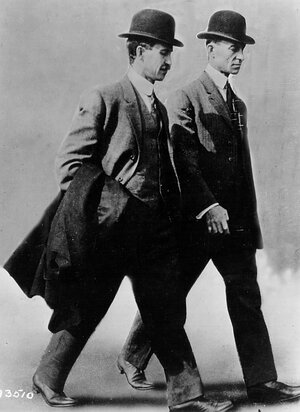 Brothers and aviation pioneers Orville and Wilbur Wright walk together in 1910.