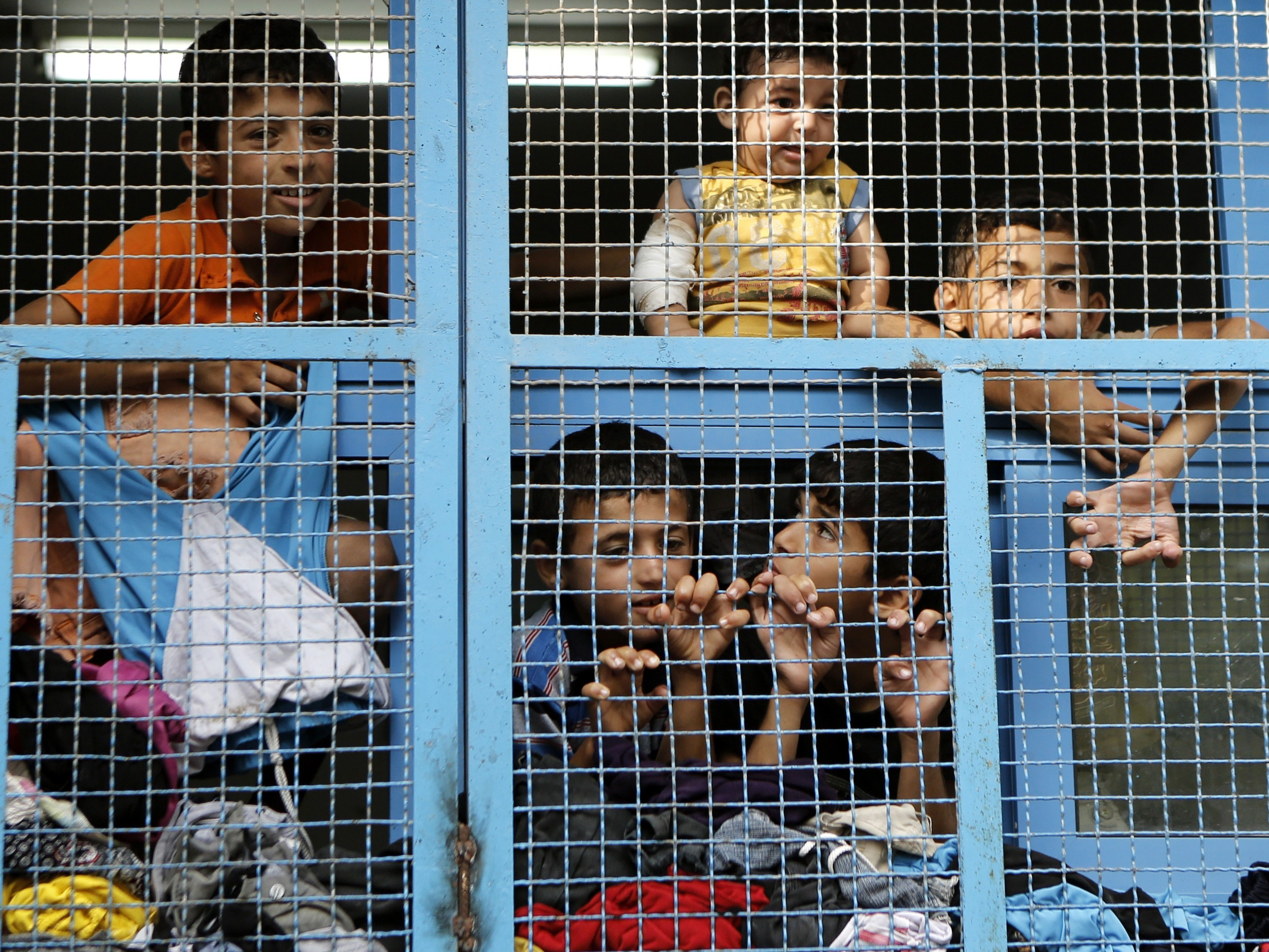 Displaced Palestinian children from Beit Hanoun in the northern Gaza Strip stand behind the window of a classroom July 23 at a UN school where displaced families took refuge after fleeing heavy fighting in the Gaza Strip.
