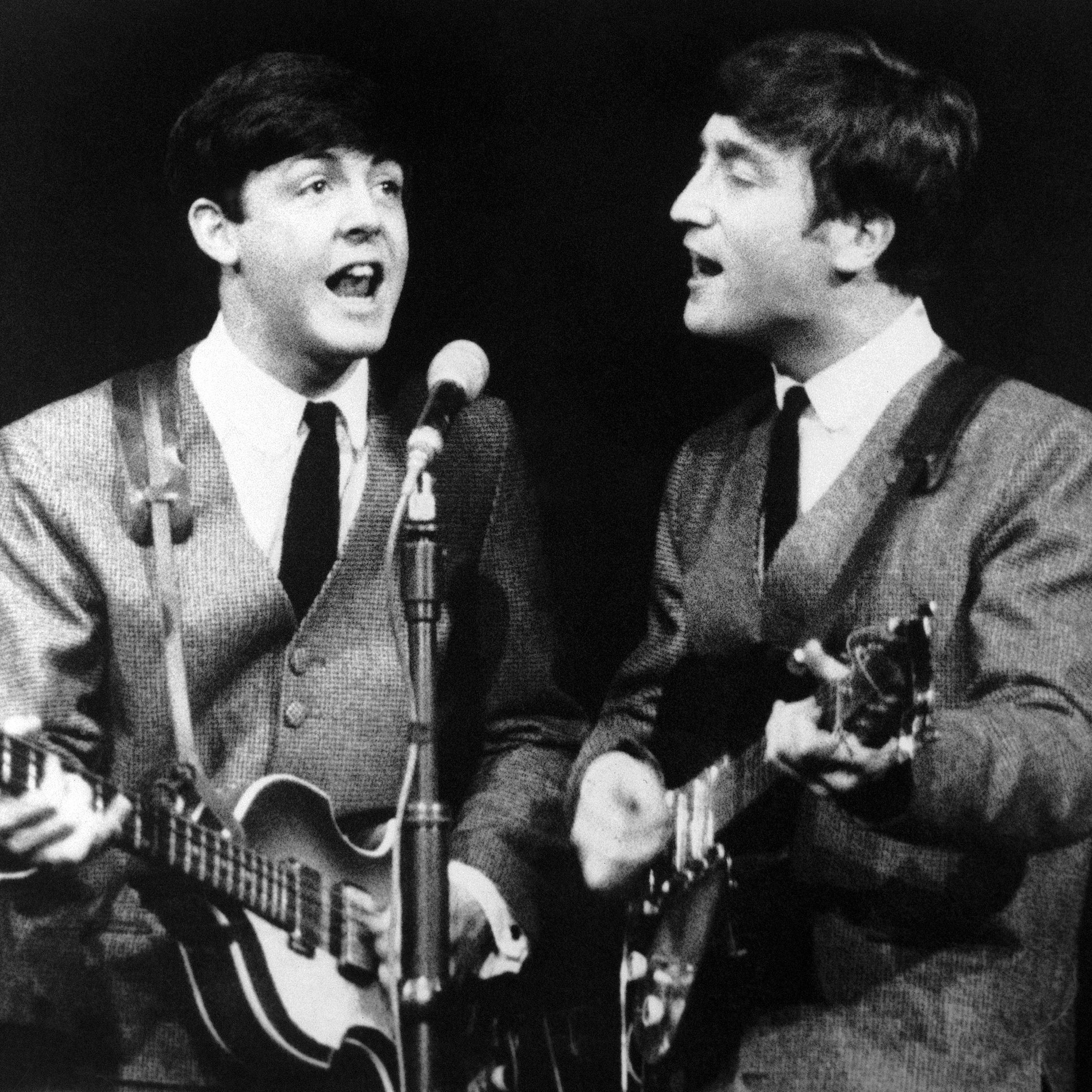 Paul McCartney, left, and John Lennon, two members of the Beatles pop group during a concert in London, on Nov. 11, 1963.