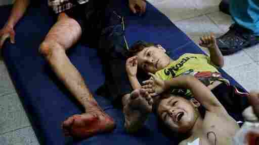 Injured Palestinian children lie on the floor of an emergency room after the U.N. schoo