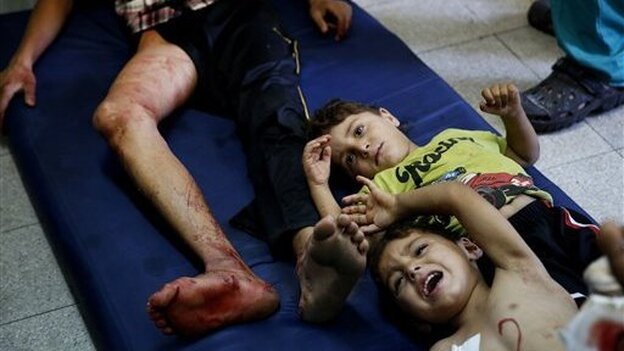 Injured Palestinian children lie on the floor of an emergency room after the U.N. school where they took refuge in the northern Gaza Strip was shelled. (AP)