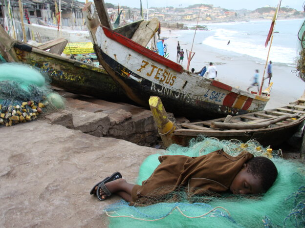 A child grabs sleep after a long day of labor in a struggling West African fishery.