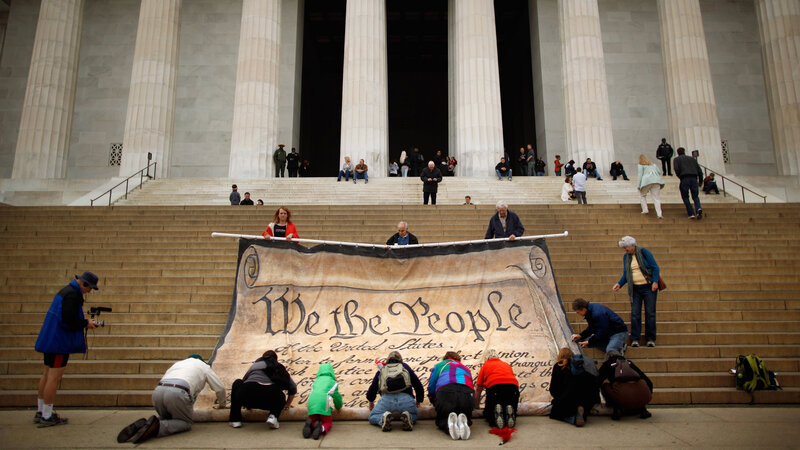Volunteers at the Lincoln Memorial help roll up a giant banner printed with the Preamble to the Constitution during an October 2010 demonstration against the Supreme Court's Citizens United ruling.