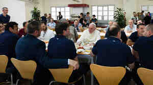 In this photo provided by the Vatican newspaper L'Osservatore Romano, Pope Francis, center, facing camera, has lunch at the Vatican workers' cafeteria, on Friday.