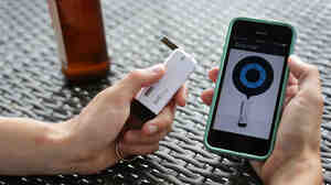 The BACTrack Vio keychain breathalyzer and app on the iPhone at NPR headquarters in Washington, D.C. A public health researcher says tools like this could help people make better decisions about alcohol use.