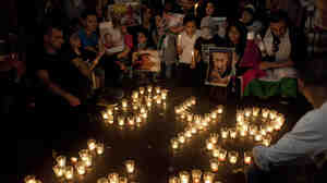 "Palestinian children, one holding a poster with a picture of Israeli Prime Minister Benjamin Netanyahu, sit next to candles forming the number 848, which they say signals the number of Palestinians killed in the ongoing war, and the word ""Gaza"" in Arabic at a protest in the West Bank city of Ramallah, Friday."