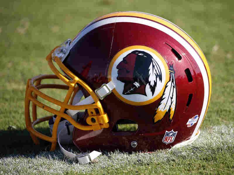 A Washington Redskins helmet lies on the turf at the football team's training facility in Richmond, Va.