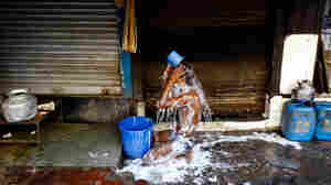 An Indian migrant worker pauses for a refreshing bucket bath on the roadside in Mumbai.