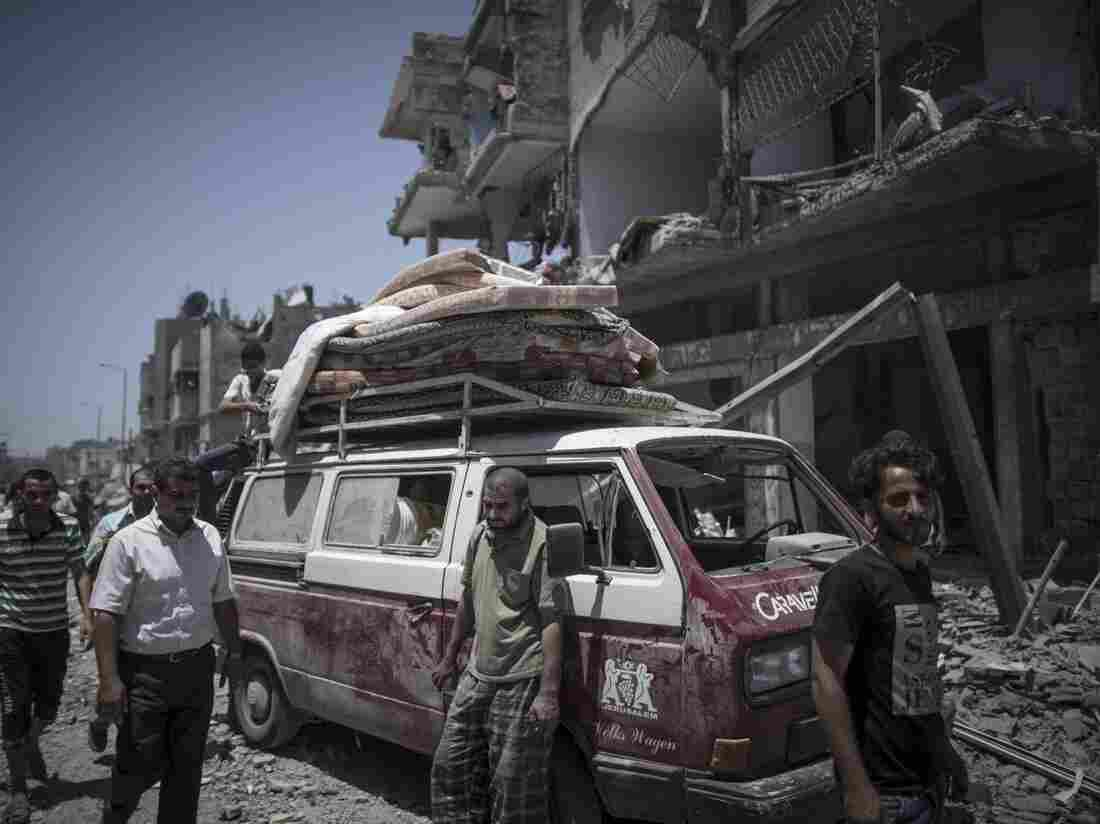 A Palestinian man leans on his car after salvaging usable items from his destroyed house in Shuja'iyya neighborhood in east Gaza City, on Saturday. Gazans are taking advantage of a brief cease-fire with Israel.