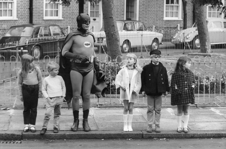"""""""What Batman provides, what all superheroes provide is this notion that good will triumph over evil,"""" says author Glen Weldon. """"That evil will have its day, but there will be somebody up there who will keep trying, who will keep looking out for us. ... He's catharsis in a cape."""" Above, Adam West, as Batman, makes a road safety film with child actors in Kensington, London in the late 1960s. (Keystone/Getty Images)"""
