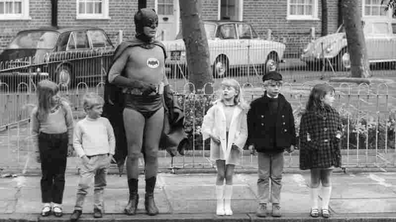 """What Batman provides, what all superheroes provide is this notion that good will triumph over evil,"" says author Glen Weldon. ""That evil will have its day, but there will be somebody up there who will keep trying, who will keep looking out for us. ... He's catharsis in a cape."" Above, Adam West, as Batman, makes a road safety film with child actors in Kensington, London in the late 1960s."