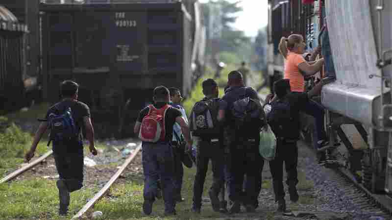 Immigrants run to jump on a train in Ixtepec, Mexico, during their journey toward the U.S.-Mexico border. President Obama wants nearly $4 billion in emergency funds to deal with the tens of thousands of children from Central America who've been crossing the border.