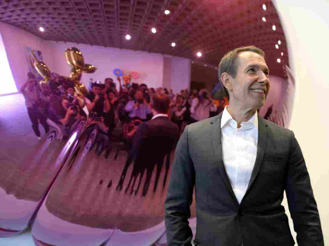 """Jeff Koons poses in front of one of his sculptures during a media preview of """"Jeff Koons: A Retrospective"""" at the Whitney Museum of American Art on June 24, 2014."""