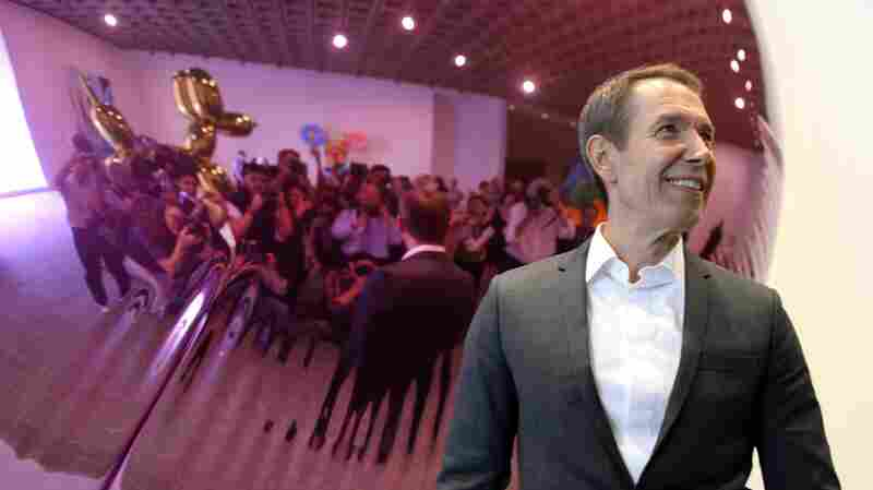 "Jeff Koons poses in front of one of his sculptures during a media preview of ""Jeff Koons: A Retrospective"" at the Whitney Museum of American Art on June 24, 2014."