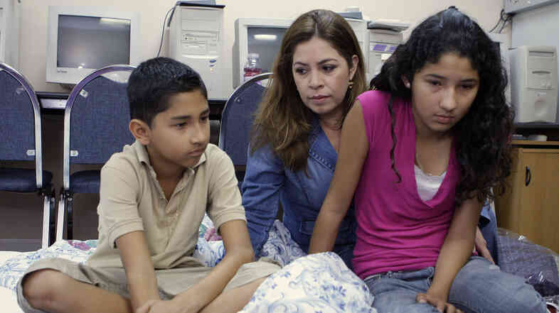 Nora Sandigo sits with Ronald Soza and his sister Cecia in 2009, while the children were on a hunger strike to protest the deportation of their mother. Sandigo is the legal guardian of the Soza children (now 15 and 18) — and 815 other American children of undocumented immigrants.