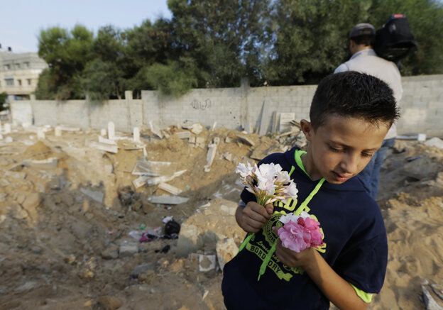 Palestinian Saeb Afana, 12, stands on the edge of a large crater from an Israeli missile strike that destroyed several graves, as he carries flowers at a cemetery in Gaza City on Monday.