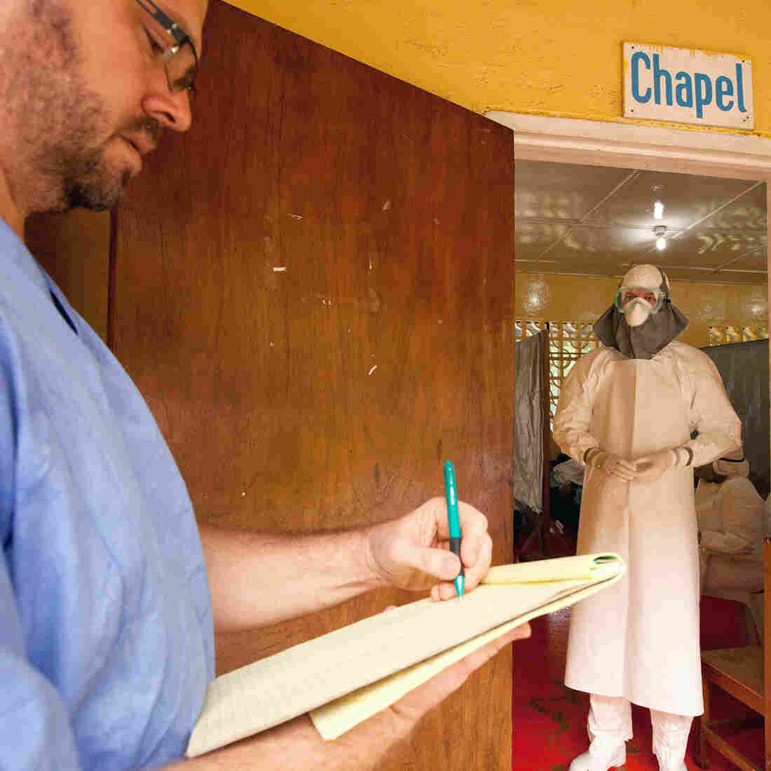 Dr. Kent Brantly (right) of Samaritan's Purse gives orders to treat Ebola patients through the doorway of the isolation ward in Monrovia, Liberia.