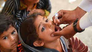 A health worker gives a child the polio vaccine in Bannu, Pakistan, June 25. More than a quarter-million children in Taliban-controlled areas are likely to miss their immunizations.