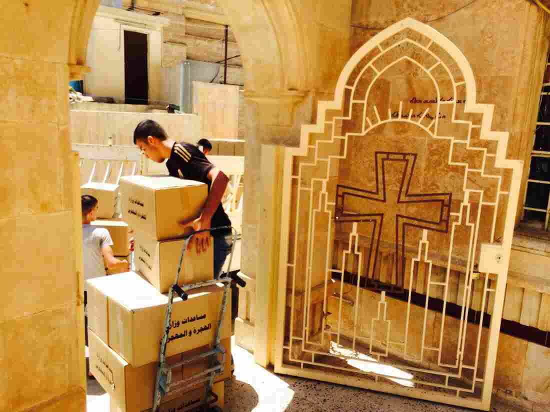 A volunteer at a Christian church in Qosh, Iraq, loads aid onto a handcart Monday for delivery to displaced Shiites who are sheltering there.