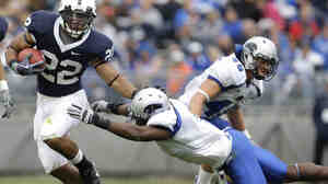 Penn State running back Evan Royster eludes a tackle by Eastern Illinois' Adrian Arrington during a 2009 NCAA college football game in State College, Pa. Arrington was one of the athletes who sued the NCAA over concussions.