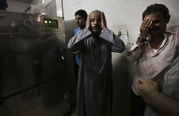 In the morgue of Gaza's Shifa hospital, Palestinian relatives mourn following an explosion that reportedly killed at least 10 people Monday, nine of them said to