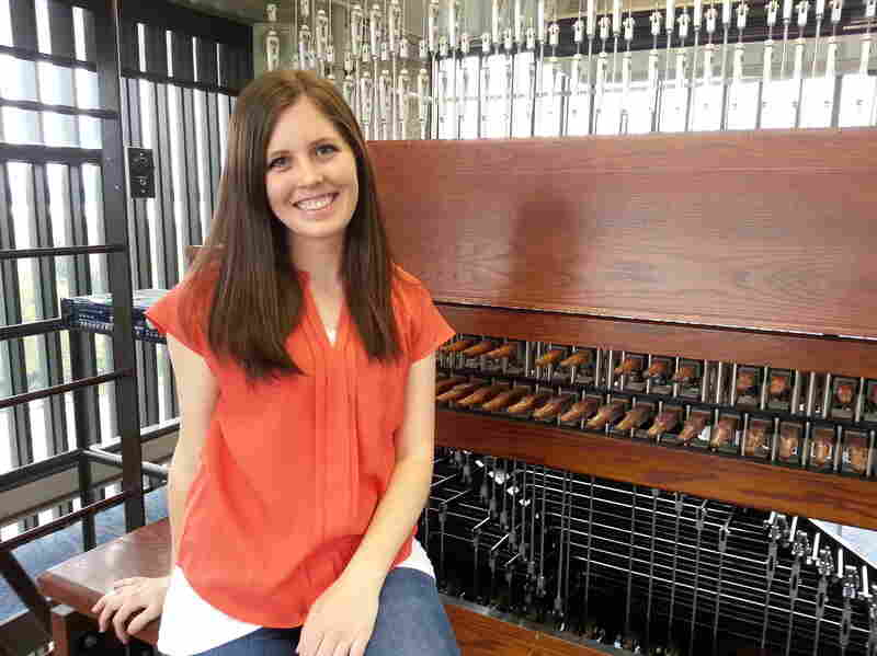 Kymberly Stone, an associate carillonneur at Brigham Young University, hits a wooden keyboard to coax music from a bell tower.