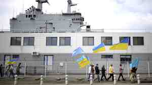 People holding Ukrainian and Crimean Tatar flags demonstrate in front of the French-built Vladivostok warship in St. Nazaire, western France, on June 1. The protesters are opposed to the sale of