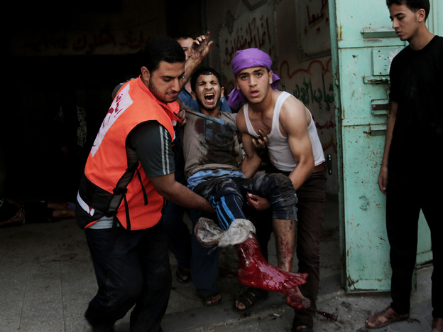 An injured man is carried to an ambulance following a strike in Gaza City's Shijaiyah neighborhood on Wednesday.