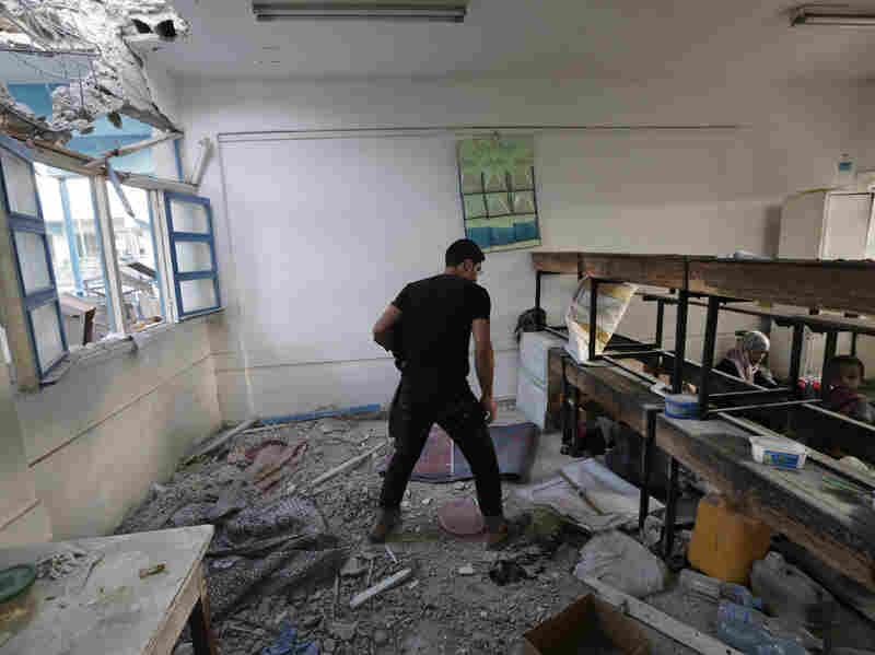 With displaced Palestinians still inside, a youth walks by the debris in a classroom at the Abu Hussein U.N. school in Jebaliya refugee camp, northern Gaza Strip, hit by an Israeli strike earlier Wednesday. Tank shells hit the school, where hundreds of Palestinians had taken refuge.