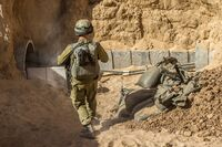 An Israeli army officer walks near the entrance of a tunnel allegedly used by Palestinian militants for cross-border attacks, at the Israel-Gaza border. A network of tunnels Palestinian militants have dug from Gaza to Israel is taking center stage in the latest war between Hamas and Israel.
