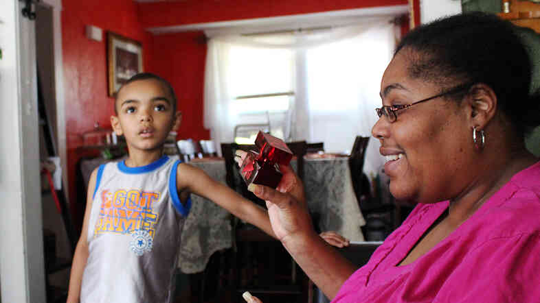 Carmen Smith, 44, shows son Roland, 6, her new perfume. The Cleveland resident says getting on Medicaid has made it much easier to manage her diabetes.