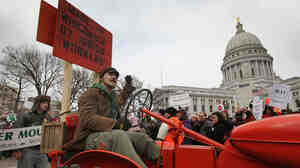 A farmer drives his tractor past the Wisconsin State Capitol during a rally in March of 2011.