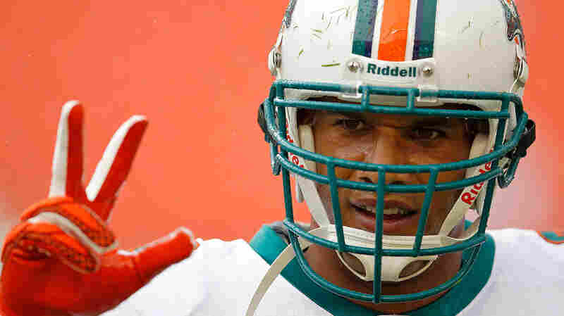 Jason Taylor signals to his teammates during a game in 2011. Those fingers endured more than a few dislocations during his NFL career.
