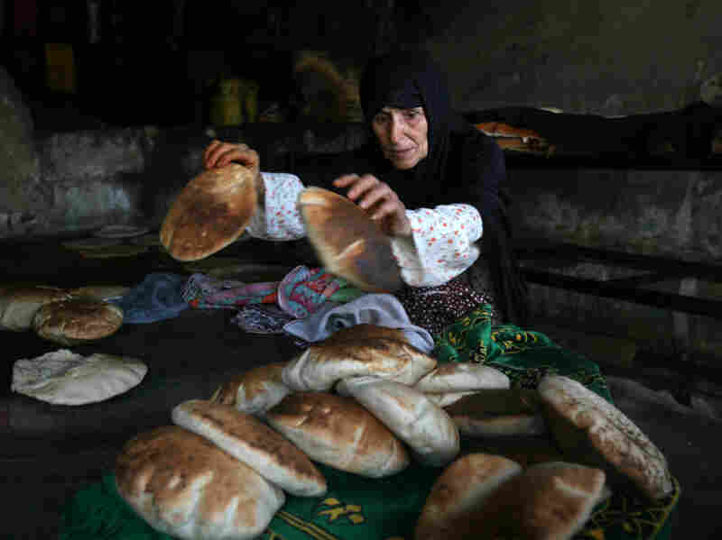 A Palestinian woman bakes bread in a traditional bakery stove in Rafah in the southern Gaza Strip on July 27.