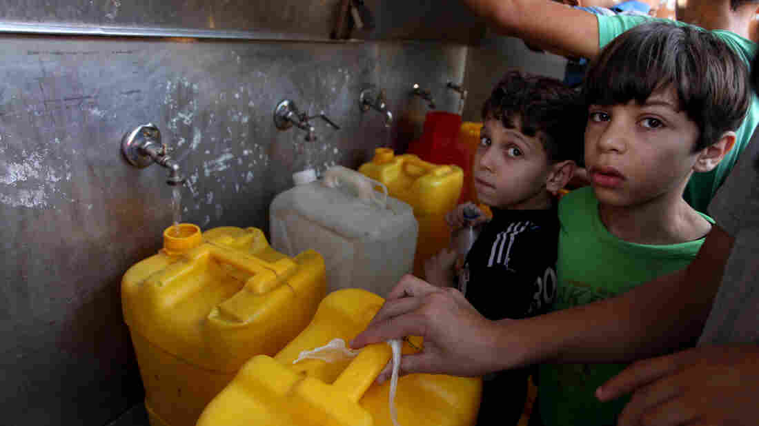 Palestinian children fill plastic bottles and water containers with drinking water from a public tap in Jabalia in the northern Gaza Strip on July 27.