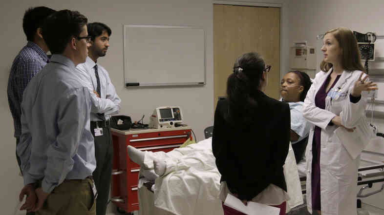 "Chief Medical Resident Dr. Julia Vermylen, right, critiques interns during an ""intern boot camp,"" held at Chicago's Northwestern Memorial Hospital in June."