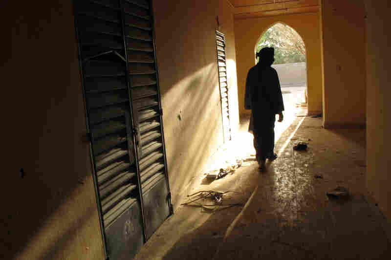 A neighborhood resident walks through a building in Timbuktu, used by al-Qaida-linked jihadi fighters for more than a year. Last year, The Associated Press found al-Qaida documents in the building.