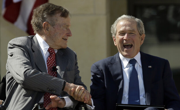George H.W. Bush (left) congratulates his son George W. Bush as the two former presidents attend last year's dedication of the George W. Bush Presidential Center
