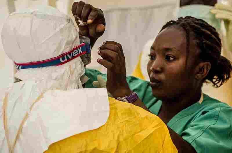 A nurse helps health workers suit up before treating Ebola patients at an isolation ward run by Doctors Without Borders in Kailahun, Sierra Leone.